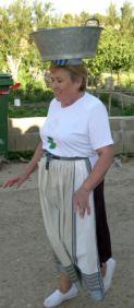 Una de las participantes llevando el balde de la ropa con tiento